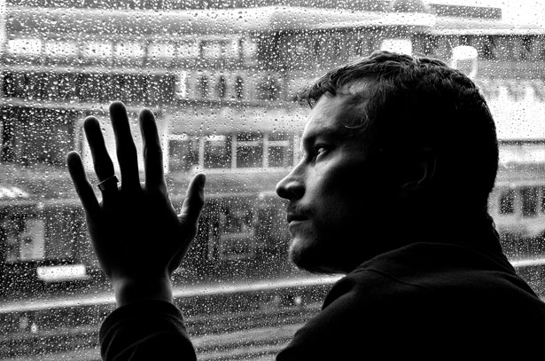 man looking out the window at rain